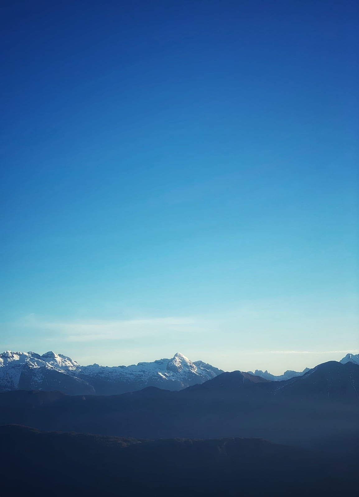A clear blue sky early in the morning over a mountain range