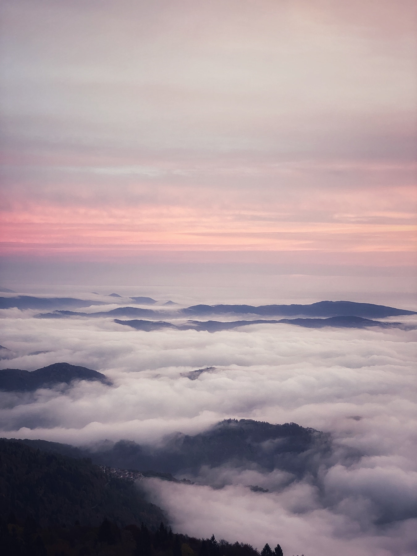 The phenomenon of thermal inversion with a sea of clouds resting over the mountains during a pink sunset