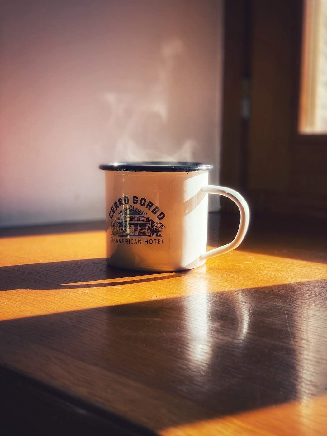 An enamelware cup resting on a table with steaming coffee in it lit by the sun shining through the window
